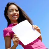 Girl with blank sign in field. Girl with blank sign standing in a field royalty free stock photos