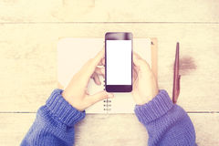 Girl with blank smartphone screen and diary on wooden table Stock Photography
