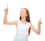 Girl in blank white shirt pointing to something Royalty Free Stock Photography