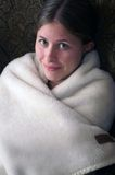Girl in blanket. Young cute woman wrapped in a white furry blanket smiling at camera Stock Photo