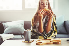 Girl in blanket relaxing on couch in living room Royalty Free Stock Photo