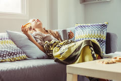 Girl in blanket relaxing on couch in living room Stock Photo