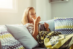 Girl in blanket relaxing on couch in living room. 10 years old pre teen girl wrapped in blanket relaxing with cocoa and breakfast on a couch in living room Royalty Free Stock Photography