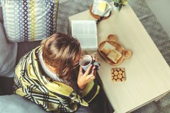 Girl in blanket relaxing on couch in living room Royalty Free Stock Images