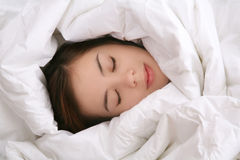 Girl in Blanket Sleeping. A young woman sleeping under a blanket Royalty Free Stock Photos