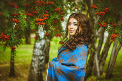 The girl in the blanket on the street. Girl standing in the blanket under the red berries Royalty Free Stock Photos