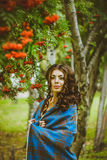 The girl in the blanket on the street. Girl standing in the blanket under the red berries Royalty Free Stock Photo