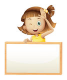 A girl blinking her eye holding an empty board Royalty Free Stock Images