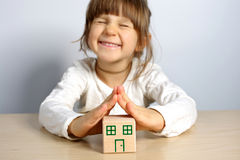 Girl with block. Little girl showing the roof of the wooden house Royalty Free Stock Photography