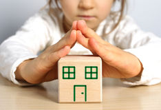 Girl with block. Small hands showing the roof of the wooden house Stock Image