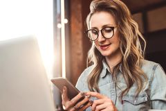 Girl blogger in trendy glasses sits in cafe and uses smartphone,checks e-mail,communicates with followers,reads news. Girl blogger in trendy glasses sits in stock photography