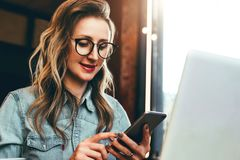 Girl blogger in trendy glasses sits in cafe and uses smartphone,checks e-mail,communicates with followers,reads news. royalty free stock photos