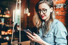 Girl blogger in trendy glasses sits in cafe and uses smartphone,checks e-mail,communicates with followers,reads news. Girl blogger in trendy glasses sits in stock image