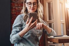Girl blogger in trendy glasses sits in cafe and uses smartphone,checks e-mail,communicates with followers,reads news. Girl blogger in trendy glasses sits in stock photo