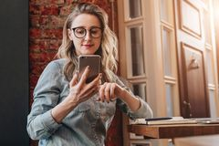 Girl blogger in trendy glasses sits in cafe and uses smartphone,checks e-mail,communicates with followers,reads news. Girl blogger in trendy glasses sits in royalty free stock photo