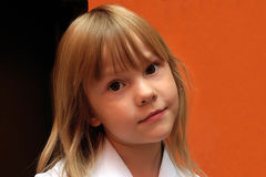 Girl blond. Portrait the girl on an orange background Stock Photos