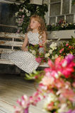 Girl with blond curly hair on a bench with flowers Royalty Free Stock Photo