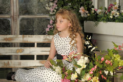 Girl with blond curly hair on a bench with flowers Royalty Free Stock Photography