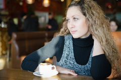 Girl with blond curly hair, drinking a cappuccino Stock Photos