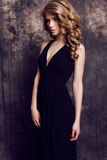 Girl with blond curly hair wearing elegant black dress Royalty Free Stock Photos