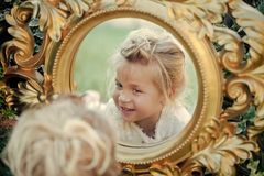 Girl with blond hair, adorable face reflect in mirror. In golden frame. Child, childhood concept. Beauty, fashion, look royalty free stock photo