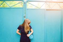 Girl with blond hair, blue Polo shirt, iron gate. The young woman looks down at her backpack. The concept of education stock image