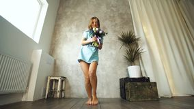 Girl with blond hair and a bunch of flowers tulips, roses, on a gray background stock footage