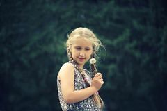 Girl with blond hair with dandelion green abstract background. stock images