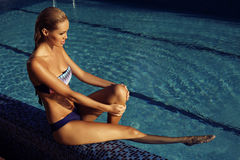 Girl with blond hair in elegant bikini relaxing in swimming pool Royalty Free Stock Image