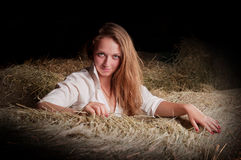 Girl with blond hair is in the hayloft Royalty Free Stock Image