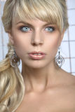 Girl with blond hair and large earrings Stock Photos