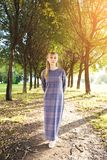 A girl with blond hair, a long striped dress, on a summer day. A young woman with a calm look, looking at the camera, against the royalty free stock photo