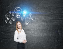Girl with blond hair near blackboard with blue light bulbs Royalty Free Stock Image