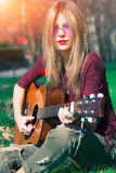 Girl with blond hair playing guitar stock photo