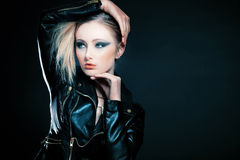 Girl with blond hair posing on black background. Royalty Free Stock Photos
