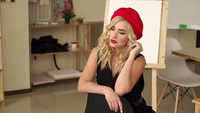 Girl with blond hair in red hat and black dress posing in the studio of drawing stock video