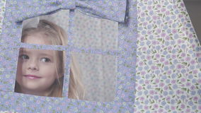 Girl with blond hair sitting in a toy house and looks out the window stock footage
