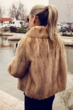 Girl with blond hair wearing luxurious fur coat Royalty Free Stock Photo