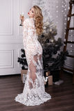 Girl with blond hair wears luxurious dress,posing beside Christmas tree Stock Photo