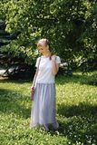 A girl with blond hair, a white t-shirt and a long skirt, on a Sunny summer day. The young woman smiles, looking down, against the royalty free stock photo