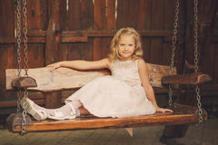 Girl with blond hair on wooden swing. Portrait of a girl with blond hair on wooden swing. Happy child, cute little baby or toddler girl with blonde curly hair Stock Images