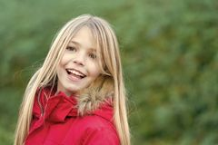 Girl with blond long hair smile on natural environment. Innocence, purity and youth. Beauty, nature, growth. Child in red coat enjoy idyllic autumn day. Happy stock images