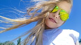 Girl with blond long hair and yellow sunglasses. Stock Image