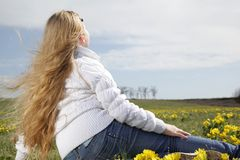 Girl  blond sitting in a field with yellow flowers. Raised her head to the sunlight Royalty Free Stock Images
