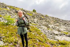girl blond tourist in a green jacket and with a backpack standing on the mountain resting, looking at the view, against stock image