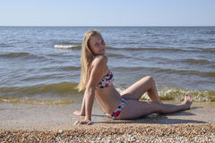 The girl the blonde in a bikini sitting on the beach in the sand. Beautiful young woman in a colorful bikini on sea background Stock Photography