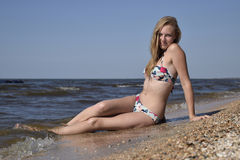 The girl the blonde in a bikini sitting on the beach in the sand. Beautiful young woman in a colorful bikini on sea background Royalty Free Stock Photo