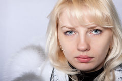 The girl the blonde blue eyes. In a fur coat on the isolated white Stock Images