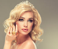 Girl with blonde curly hair with a big rings. Stock Photos