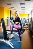 Girl blonde doing exercises in the gym. Girl goes in for sports in the gym. Concept of a healthy lifestyle. stock photos
